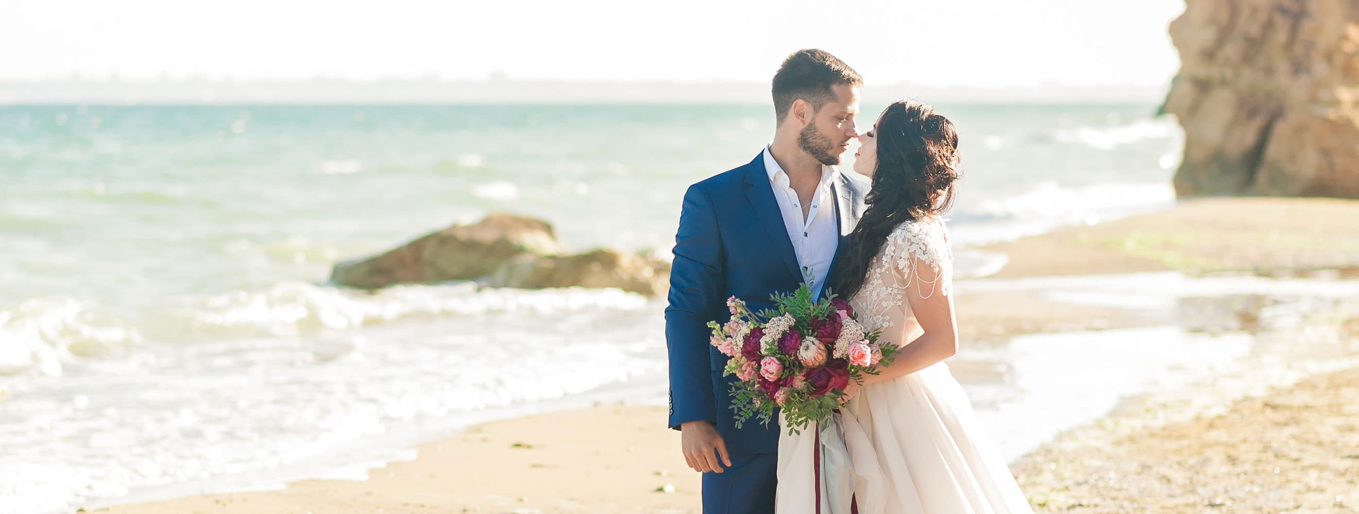 Bride and Groom look intensely into each others' eyes on the beach