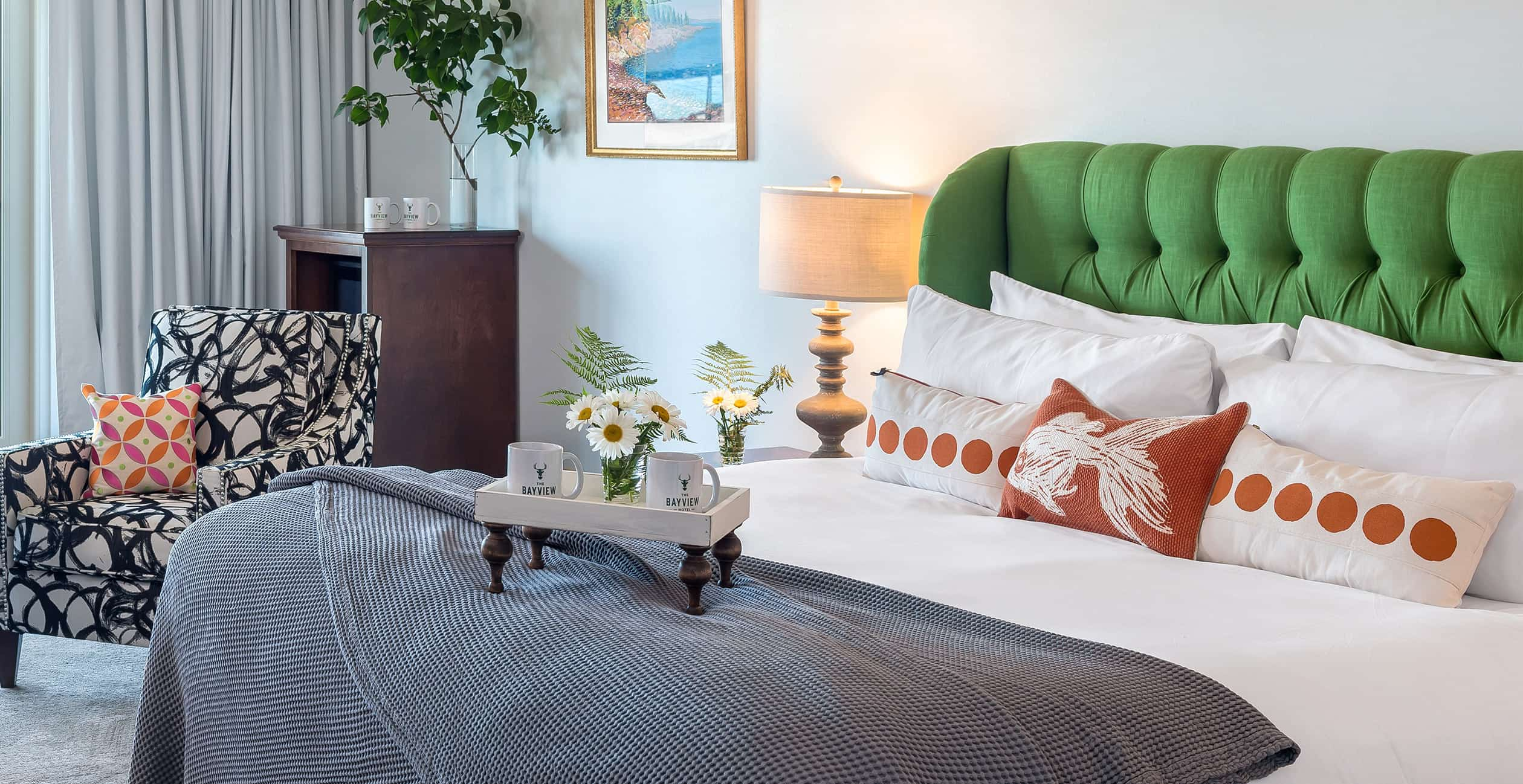 King bed with green headboard and clean linens