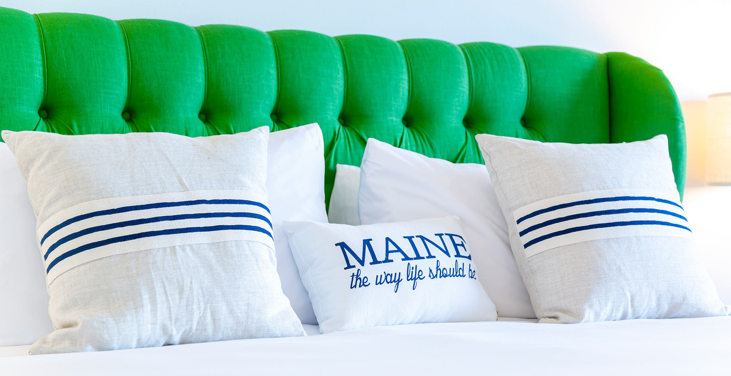 "King bed with green headboard and text ""Maine the way life should be"""