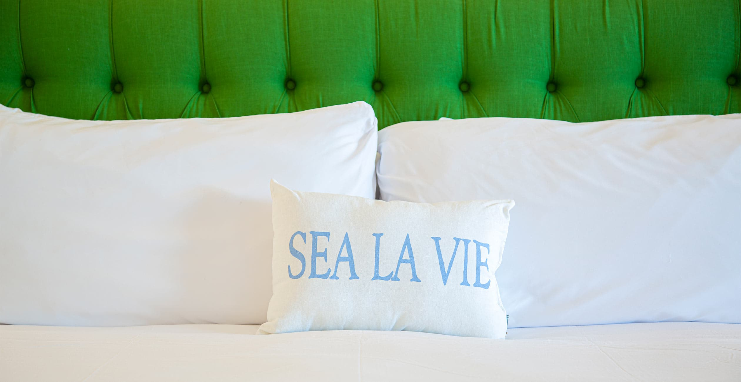 "Bed featured pillow with words ""Sea La Vie"""