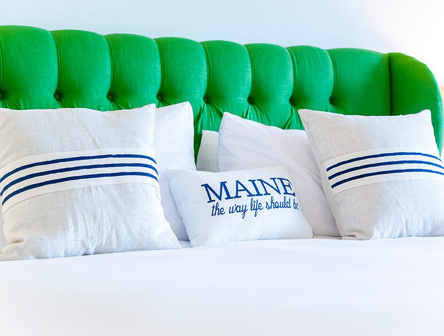 "Bed with green headboard and text ""Maine the way life should be"""